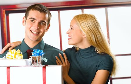 Young happy couple or business people with gift boxes photo