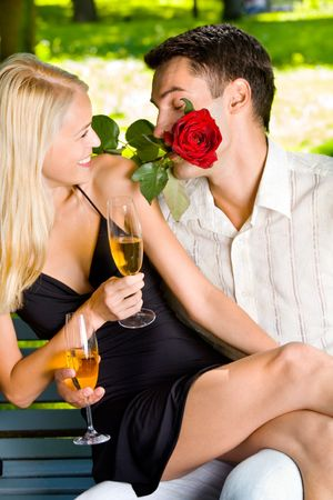 Funny scene of couple celebrating with champagne and rosa, outdoors photo