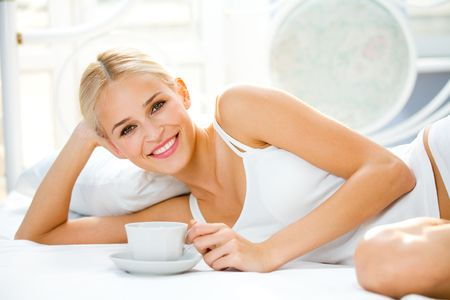 Portrait of beautiful woman with cup on bed at bedroom photo