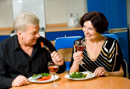 Elderly happy smiling couple eating together at home photo