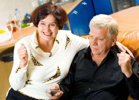 Mature happy smiling couple watching TV together at home Stock Photo - 1934357