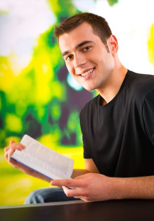 Portrait of young happy man reading book, outdoors photo