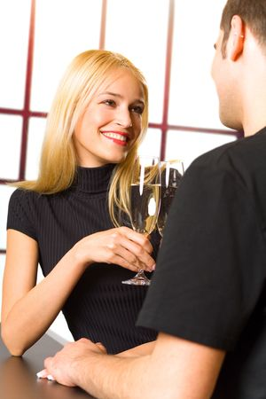 Young couple celebrating with champagne together. Focus on woman. photo