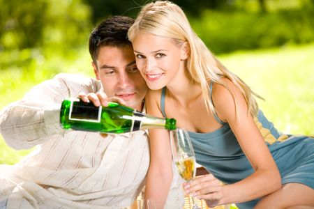 Young couple celebrating with champagne together, outdoors photo