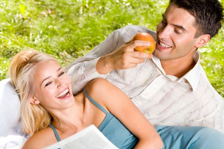 Young happy couple eating apples and reading newspaper outdoors photo