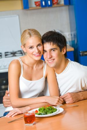 vegetables young couple: Young happy amorous couple at domestic kitchen