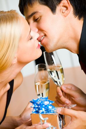 Young happy couple with gift and champagne kissing at restaurant