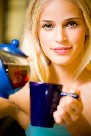 Young beautiful happy woman with teapot, indoors. Focus on woman. Stock Photo - 2097725