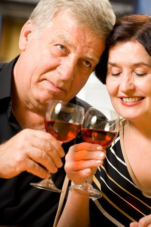 Elderly happy smiling couple celebrating with red wine at home photo