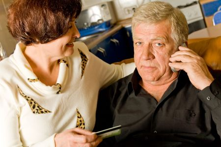 Mature couple on cellphone shopping with credit card