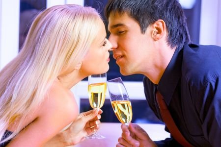 Young happy couple with champagne kissing at restaurant photo