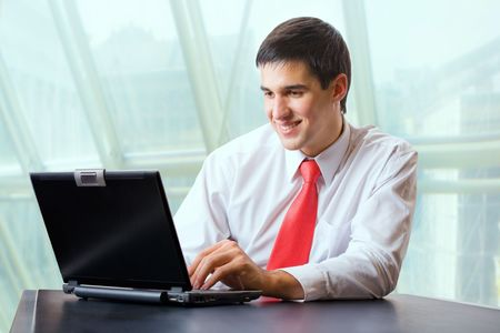 Young happy businessman or student on laptop photo