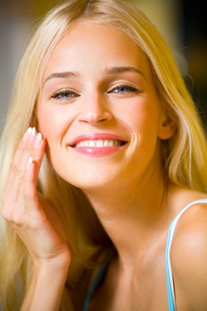 antiaging: Portrait of young beautiful woman applying creme Stock Photo
