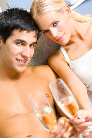 sexual activities: Young happy couple celebrating with champagne at bedroom