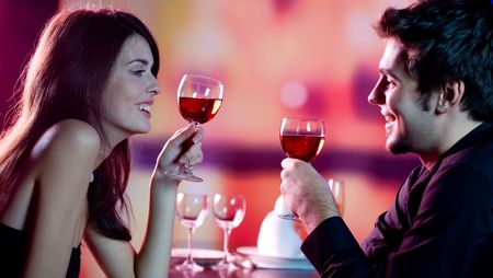 Young happy amorous couple celebrating with red wine at restaurant photo