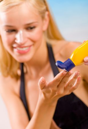 Young happy smiling woman with sun-protection cream on beach. Focus on cream. photo