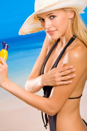Young happy smiling woman with sun-protection cream on beach photo