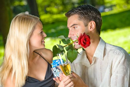 Funny young happy couple with gift and rosa, outdoors  photo
