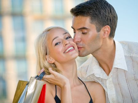 amorous: Young attractive happy amorous couple with shopping bags outdoors Stock Photo