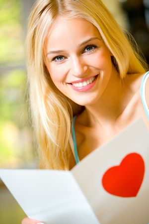 Portrait of young attractive happy woman, reading valentine card photo