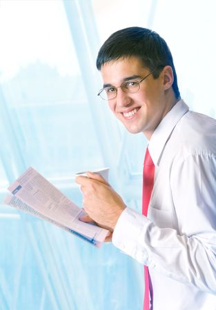 Businessman reading newspaper with tea or coffee at office Stock Photo - 2487887