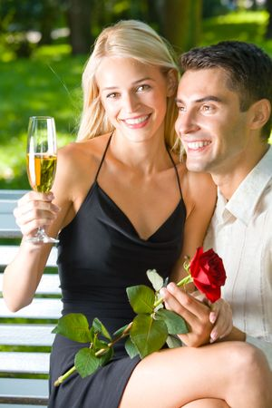 Young happy couple with champagne, gift and rose, outdoors  photo