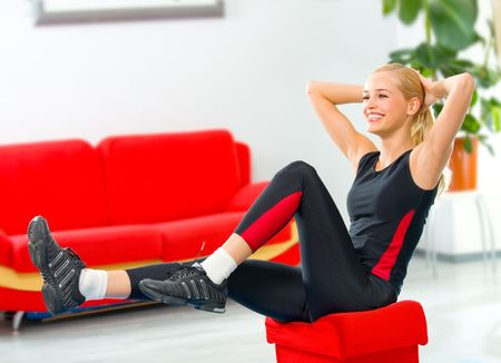 Young happy smiling woman doing fitness exercises at home Stock Photo - 2557394