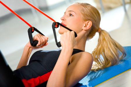 expander: Young woman doing fitness exercises with expander at home