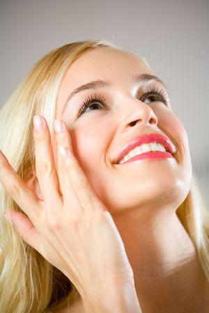 mujer maquillandose: Retrato de la mujer feliz joven que aplica maquillaje