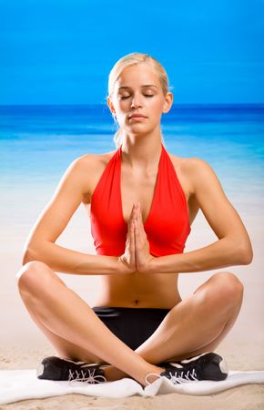 Young woman doing yoga moves or meditating on sea beach photo