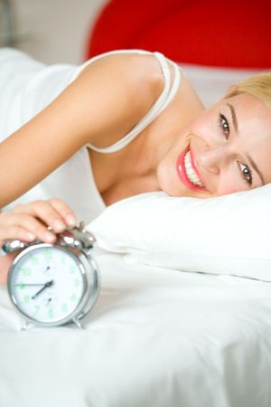 alarmclock: Young woman with alarmclock on the bed at the morning