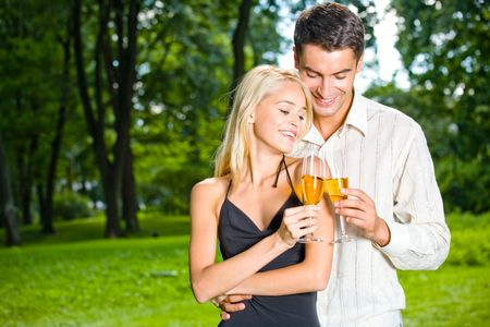 Young happy couple celebrating with champagne, outdoors photo