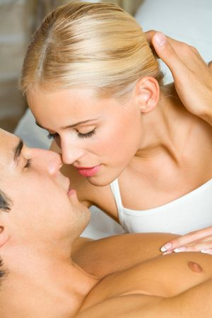 Portrait of young amorous couple kissing at bedroom Stock Photo - 2776024