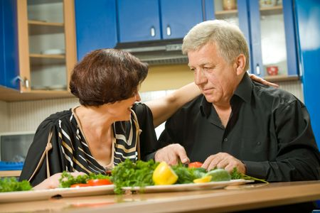 Elderly happy attractive smiling couple cooking at kitchen photo