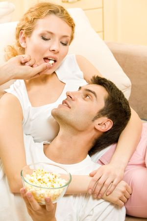 Young happy couple eating popcorn together at home photo