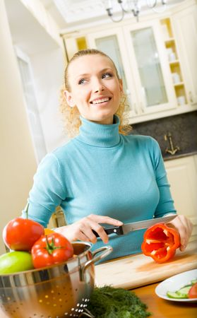 Young happy woman making salad at domestic kitchen Stock Photo - 2900231