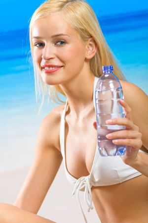 Young beautiful happy woman with bottle of water on beach photo