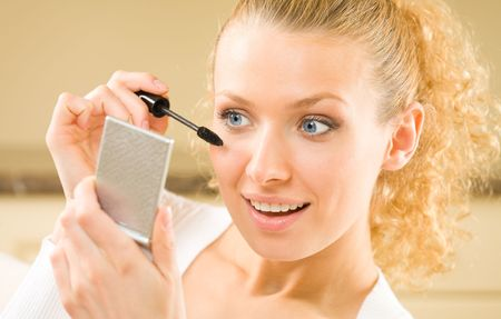 Portrait of young woman applying mascara with mirror photo