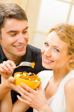 Young happy couple eating salad at home together photo