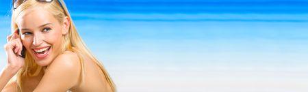 eslogan: Joven rubia hermosa mujer con m�vil en la playa. Para ofrecer la m�xima calidad, he hecho esta imagen por combinaci�n de tres fotos. Puede utilizar parte derecha de eslogan, grandes o banner de texto.  Foto de archivo