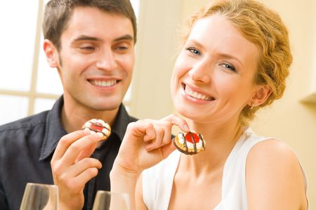 Portrait of young happy couple eating cakes at home Stock Photo - 3112947