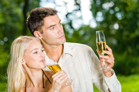Young happy couple celebrating with champagne outdoors photo
