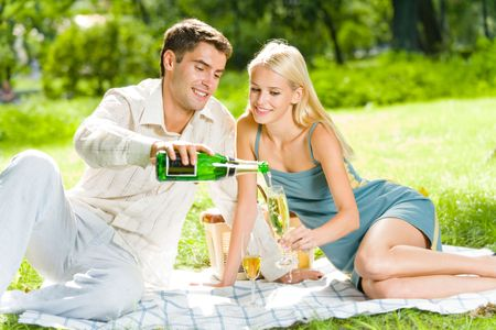 amour: Young happy couple celebrating with champagne at picnic
