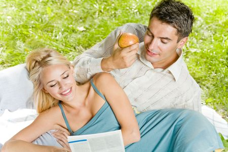 Young happy couple reading together newspaper outdoors photo