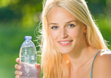 Portrait of beautiful smiling woman with bottle of water, outdoors photo