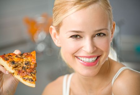Portrait of young woman with pizza at kitchen photo