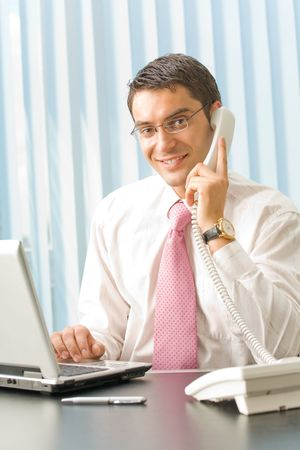 Happy smiling businessman with laptop and phone at office Stock Photo - 3214216