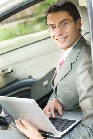 tecnology: Happy smiling businessman using laptop in car