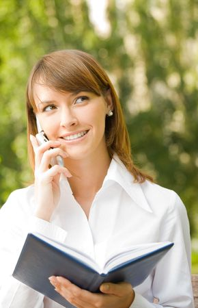Happy smiling successful businesswoman with cellphone and notebook outdoors Stock Photo - 3324863