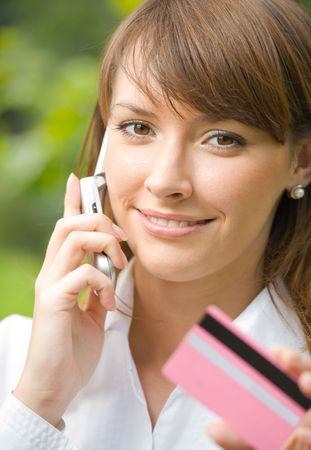 Young happy woman with cellphone paying by credit card  photo